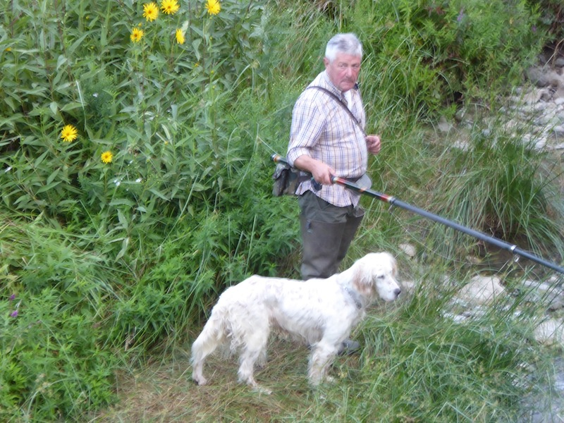 A man was fishing with his dog.