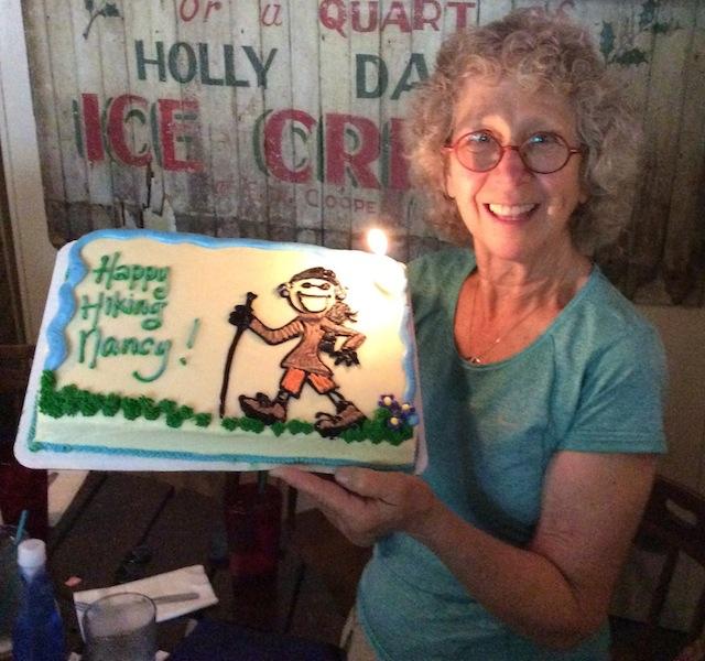Nancy holds cake that says happy hiking Nancy.