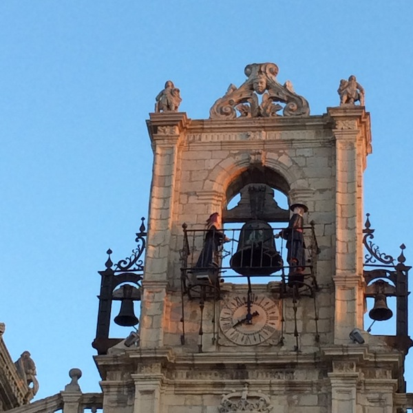 Two sculpted figures are striking the bell in Astorga.