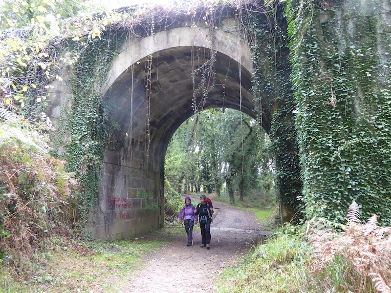 Rose and Mary walking under a bridge on way to Negreira.