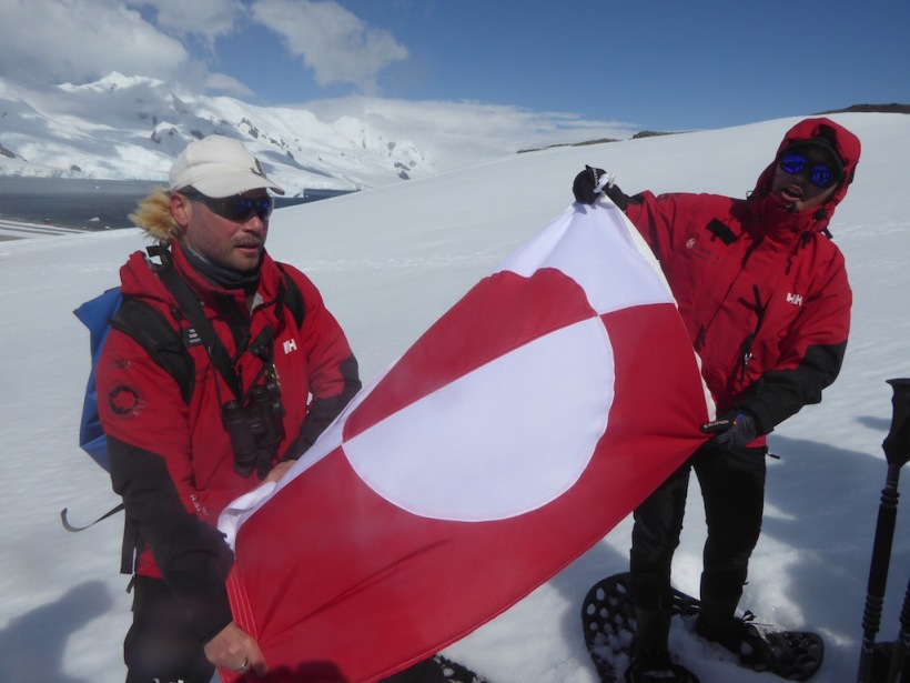 Greenland Flag is held up on Half Moon Island.