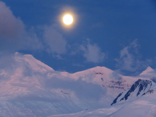 The full moon is shining over the glaciers.