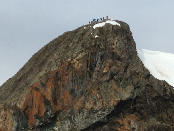 The people look like ants on the top of the hill.